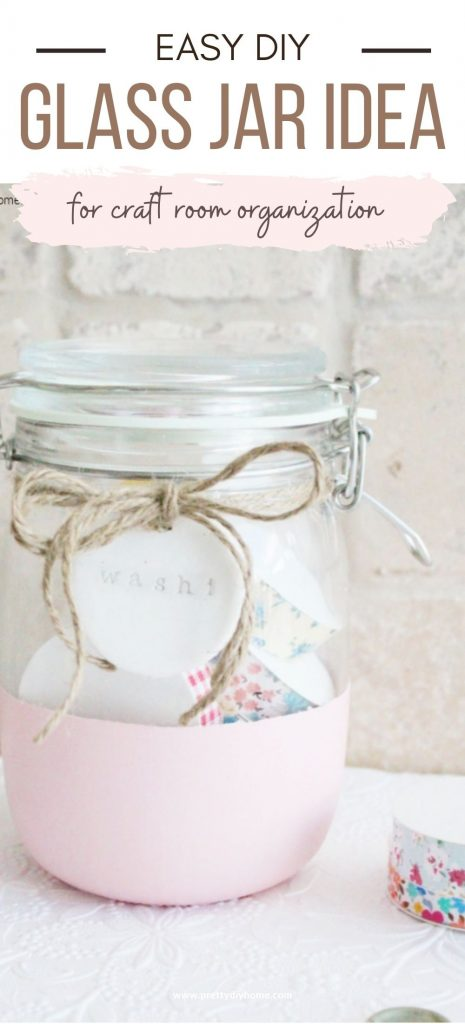 An easy to paint DIY glass jar craft idea. A clear jar with the bottom painted pink then tied with a twine bow, and filled with Washi tape. A fun, simple, and inexpensive craft room and home office organization idea.
