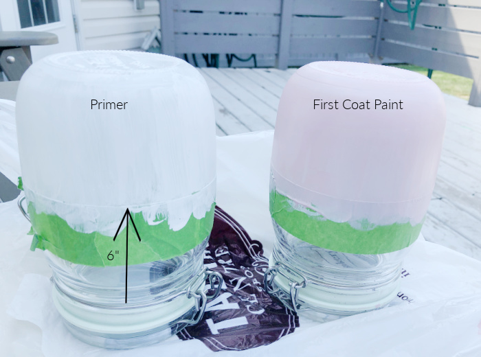 Two mason jars being taped and painted