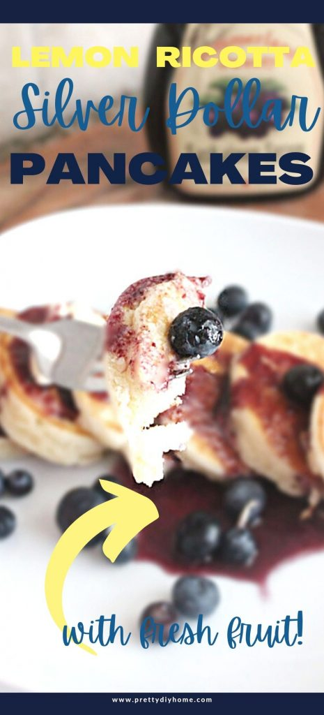 A plate of lemon ricotta silver dollar pancakes on a white plate. With a bite of pancakes with blueberries on a fork.