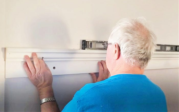 Attaching a shelf to the wall making sure it is level.