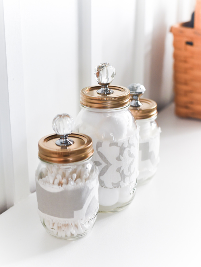 Three DIY glass storage jars for the bathroom with beautiful metallic lids and soft grey ribbon.