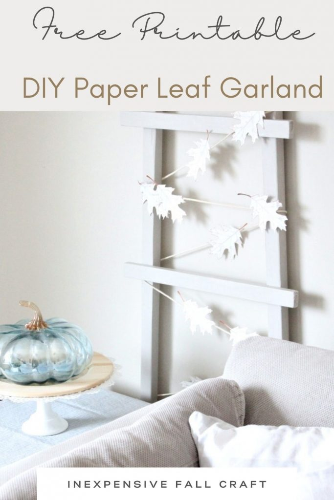 A modern farmhouse ladder strung with a DIY paper leaf banner in neutral creams. The ladder sits behind a soft grey couch and their is a soft blue pumpkin on the coffee table next to the free printable leaf banner.