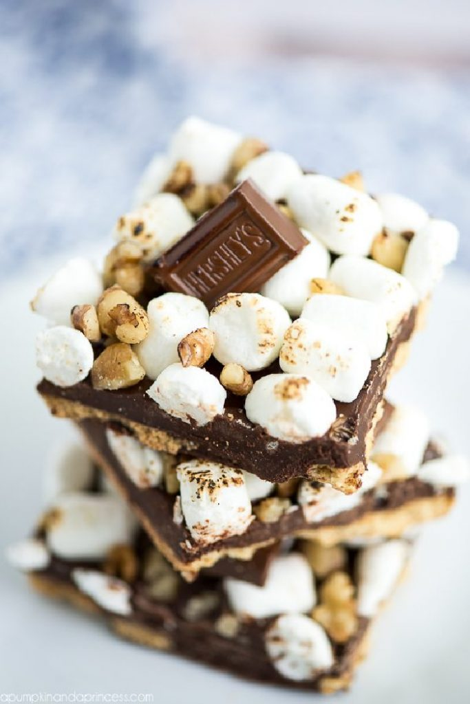 A big stack of rocky road S'more bark candy.  This homemade candy recipe has a graham crust layer, melted chocolate, topped with toasted marshmallows and hershey bar chunks.