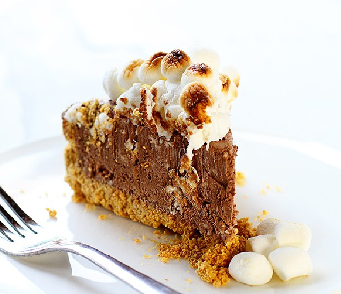 A thick slice of homemade frozen s'mores cheesecake on a white plate with a fork beside it. The cheesecake has a graham crust, thick dense layer of chocolate cheesecake filling, and toasted marshmallow topping.