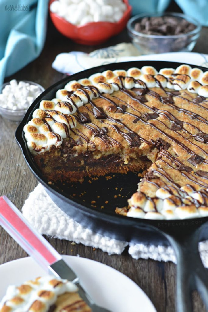 A large caste iron pan sitting on a counter filled with S'more skillet cookie. The large cookie has a slice out of the middle so you can see the layers, and it is edged with toasted mini marshmallows.