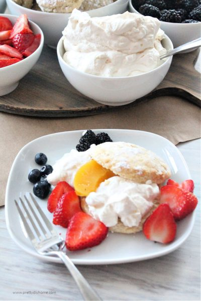 Homemade classic strawberry shortcake served with sweet biscuits, there is a dessert charcuterie board in the background with strawberries, raspberries, peaches, blackberries, blueberries and whipping cream.