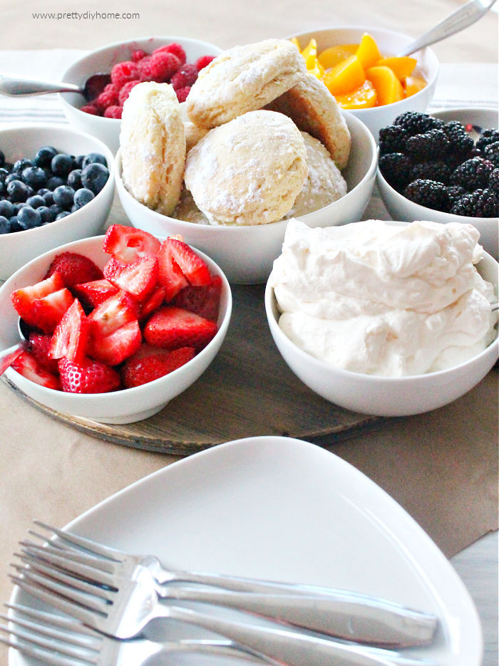 How to serve strawberry shortcake dessert charcuterie. Several small bowls with a dish of sweet biscuits in the middle surrounded by an assortment of fresh berries and whipping cream.