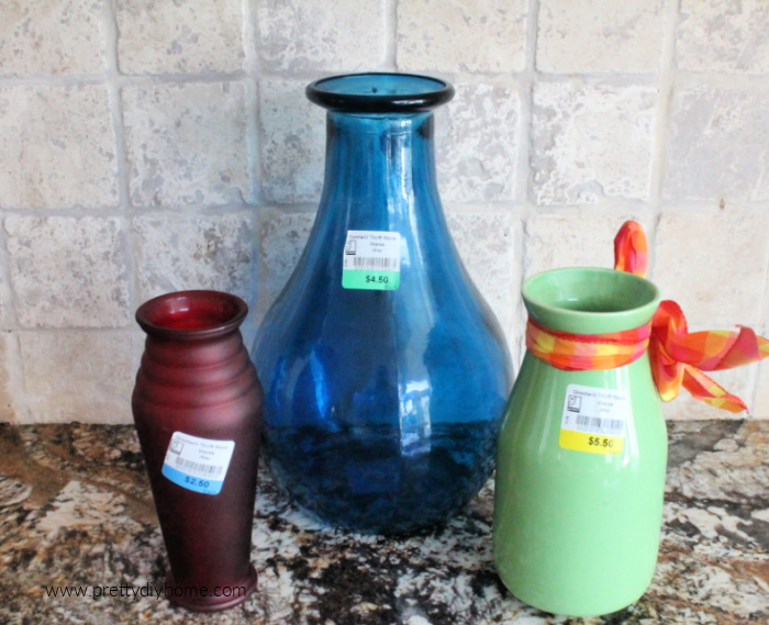 Three different thrift store vases a large blue, a medium green, and a small red vase.