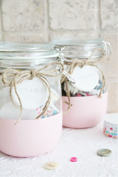Two craft room storage jars with pink painted bottoms, bright white stamped labels that say washi and buttons, that are tied on with twine bows.