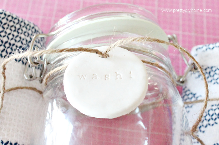 A glass jar being held in place by two towels and have a polymer clay DIY tag attached to the front with twine.