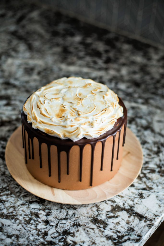 A whole entire S'mores cake with chocolare cake overed with chocolate icing, then drizzled with chocolate and then covered with melted toasted marshmallows.