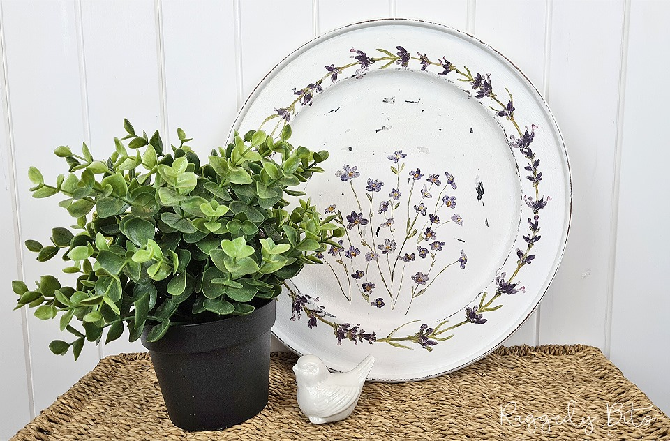 A white wooden plate covered in transfer lavendar flowers. An easy farmhouse upcycle for home decor