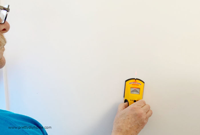 Using a stud finder for hanging pegboard shelves in the bedroom.