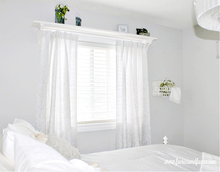 A bright wide farmhouse or cottage bedroom with a DIY window shelf and curtain rod combo. The curtain shelf is holding various small pieces of farmhouse decor.