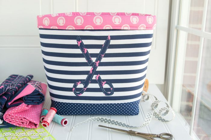 A large fabric bin with a appliqued pair of scissor on the front. The basket has a blue base, striped fabric and handmade pink brim. An easy to make large fabric basket tutorial to sew.
