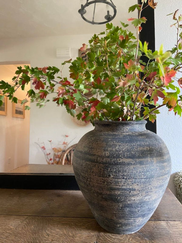 A large black and grey upcycled pottery vase holding a bouquet of orange and green leaves.