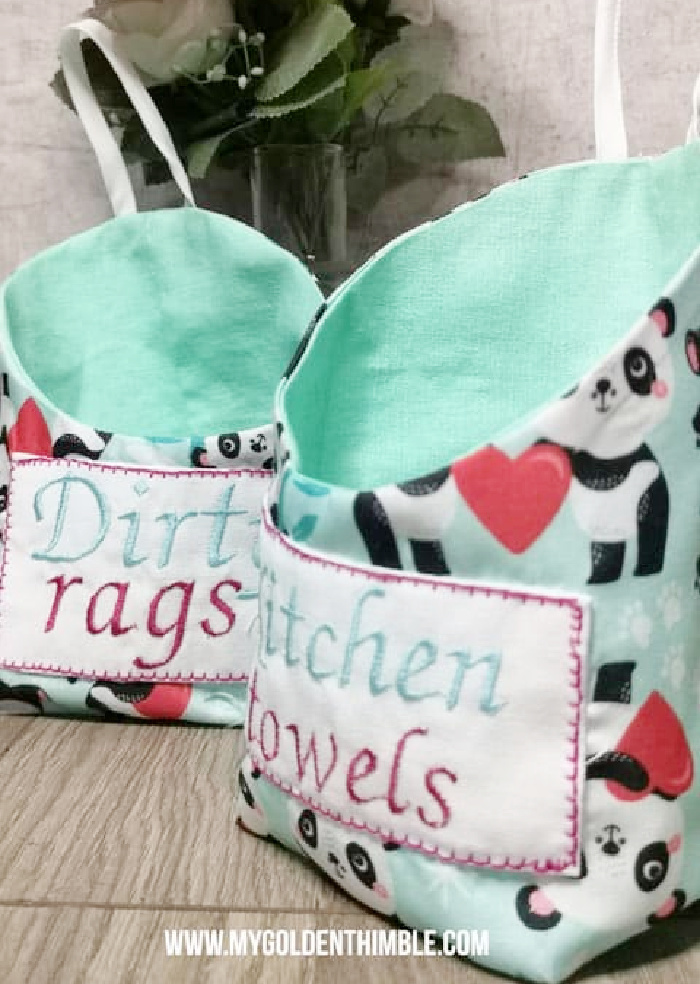 DIY fabric hanging storage bins for the kitchen. Their are two bins in green fabric, with appliqued labels, one says dirty rags, and the other says kitchen towels.