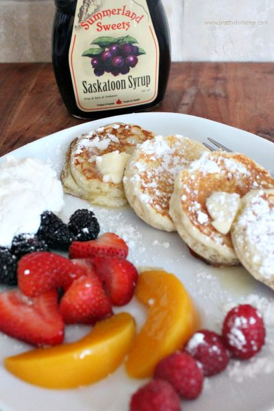 A serving of four silver dollar sized lemon ricotta pancakes dusted with icing sugar and dabs of butter. The pancakes are served on a white plate with an assortment of fresh berries, blueberries, strawberries, blackberries, raspberries and peaches in neat rows.