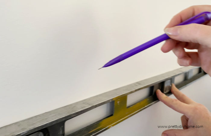 Using a level to mark shelf placement on the wall with a pencil
