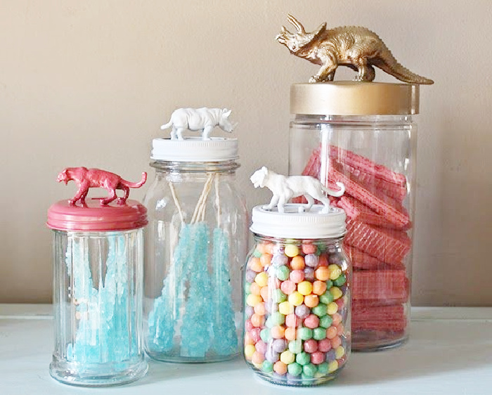 Colourful and cute DIY glass jar makeovers using various jars and small toy dinosaurs as handles on the lids.