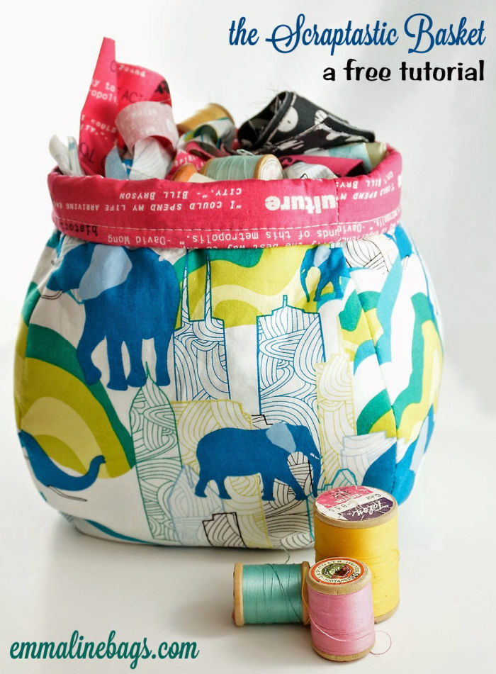A colourful rounded DIY fabric basket made with scrap fabrics. Its has yellow and blue elephant fabric, and red trim. The DIY fabric basket has a blossom shape and there is fabric inside the basket and three spools of thread in front of it.