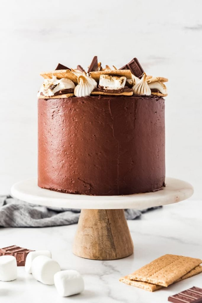 An entire S'mores cake with smooth chocolate icing on a pedestal plate.  The top of the cake is decorated with dollops of marshmallow fluff and big chunks of luscious chocolate.