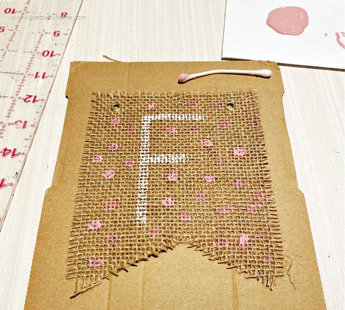 Pink Fall Banner with pink polka dots painted on Dollar Tree burlap banner kit. The letter F for the word Fall is painted on the front of the Fall bunting using white paint.