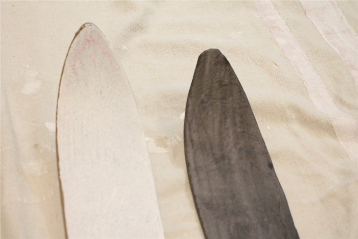 Thrift store skiis being turned into vintage wood skiis using mod podge and wood grain paper.