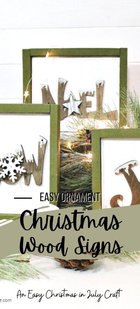 Mini wood Christmas signs using upcycled ornaments, the signs are white with green frames and are sitting on a shelf surrounded by greenery, snowball ornaments, mini lights and pine cones.