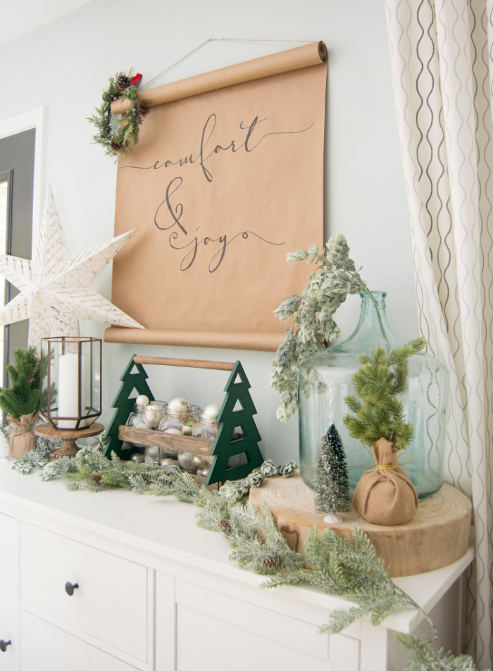 A handmade Christmas paper scroll sign that says Comfort and Joy.