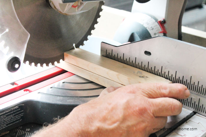 Using a radial arm saw to trim small pieces of scrap wood to size for a DIY wood frame and repurposed Christmas sign.