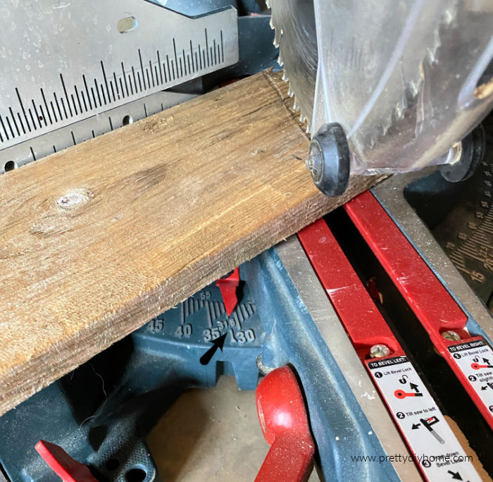 Using a large mitre saw to make angle cuts on wood pallets for making a Christmas tree. There is an arrow pointing to the spot where the angle of the cut is measured.