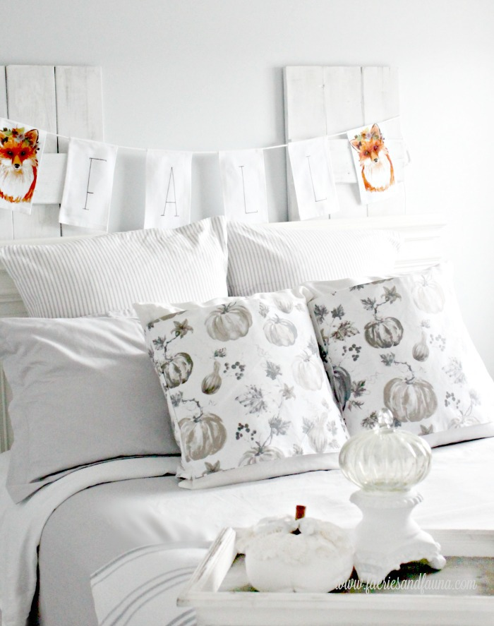 A farmhouse bedroom decorated for Fall with DIY Fall pillow wraps, and dove grey bedding. The bedroom also has white pumpkins and ticking cushions.