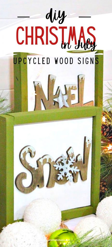 Three DIY wood Christmas signs are surrounded by greenery, faux snowballs, white starry lights, and pinecones.