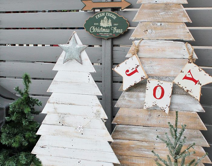Two different rustic wood pallets for Christmas, The wood pallet trees are for Christmas decor one is white and the other one is stained wood. They are decorated with simple Christmas decorations.