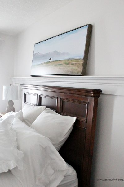 A DIY peg rail shelf made out of wood moulding that has been built to hold pictures above a bed. An easy to build DIY picture ledge for above the bed.
