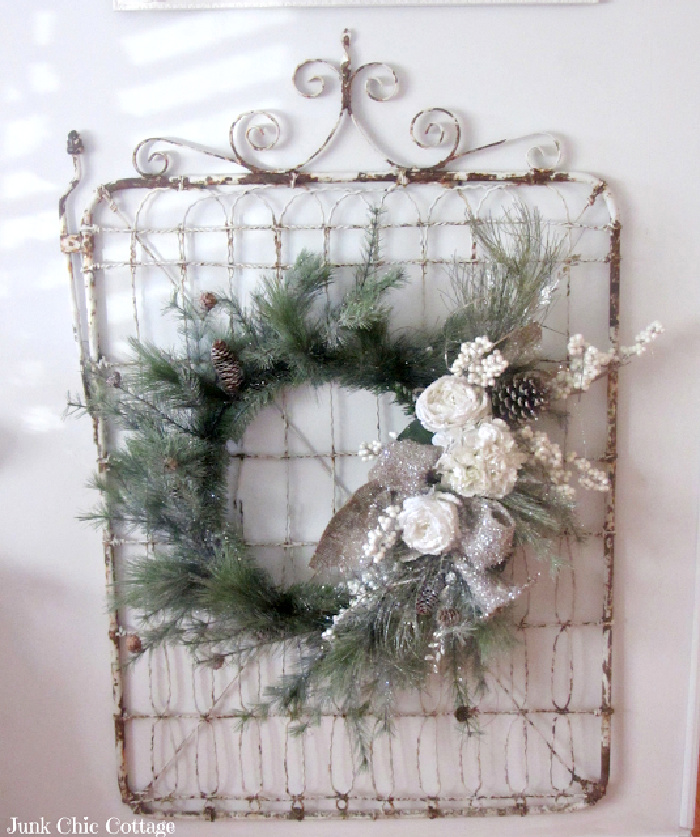 A white Christmas wall display with a vintage gate background behind a wreath and white decor.