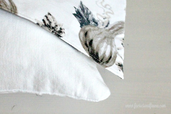 How to sew and fit DIY pillow wraps for Fall. Showing how to fit the corners of the wrap around the cushion.
