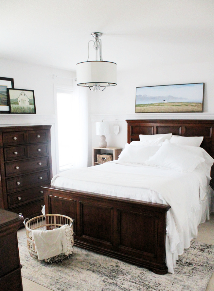 A refreshed master bedroom with DIY peg rails on the walls to hold pictures. There is white linene bedding and a vintage style bedroom furniture including a bleached wood night stand.