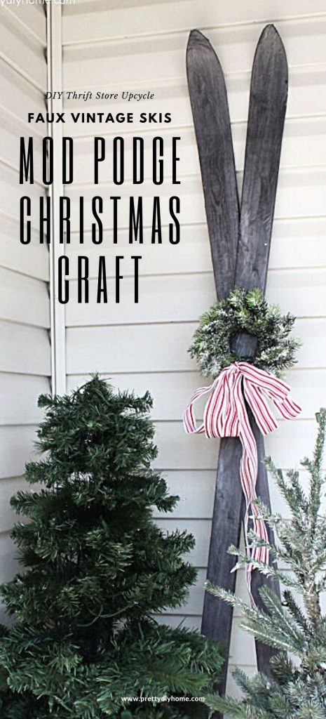 Vintage faux wood grain upcycled skiis using mod podge with a pretty miniature Christmas wreath. A DIY Christmas skiis upcycle project sits behind two pretty Christmas trees on a Christmas front porch.