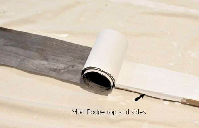 Rolling strips of wood grain paper onto skiis using mod podge.