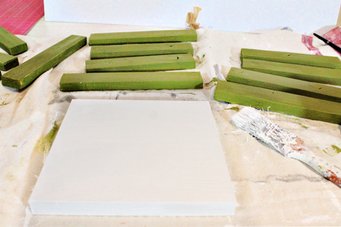 Painting wood frames with two coats of sage green paint, and a white wood square with white paint. Painting the green and white wood pieces for Christmas mini signs.