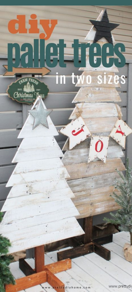 Two tall pallet wood Christmas trees sitting outside for Christmas decor. They are painted in shabby white with stained trunks and have a Christmas tree farm sign beside them.