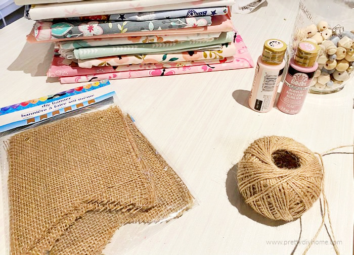 Dollar Tree burlap banner with pretty pink fabric, pink paints, gold and white beads and twine. The supplies needed for making an inexpensive yet gorgeous DIY Pink Fall Garland with lots of Girly Charm..