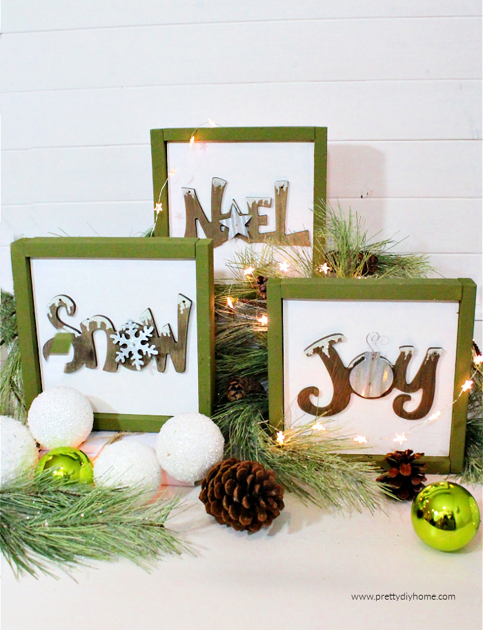 Three upcycled Christmas decorations, or Christmas mini signs. They signs are wooden with a rustic appearance, the frames are sage green with a white background and wood lettered ornaments in the center.