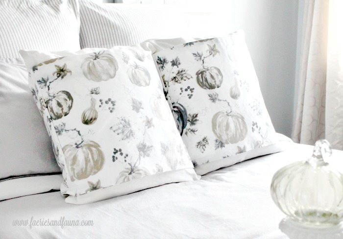Two DIY Fall Pillow Wraps in neutral colours with pumpkins and Fall leaves sitting on a farmhouse bed.