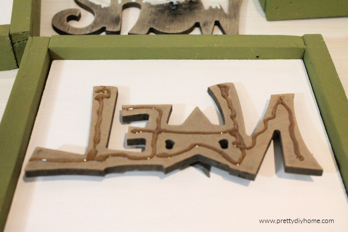 Adding glue to the back of a DIY wooden sign before attaching it.