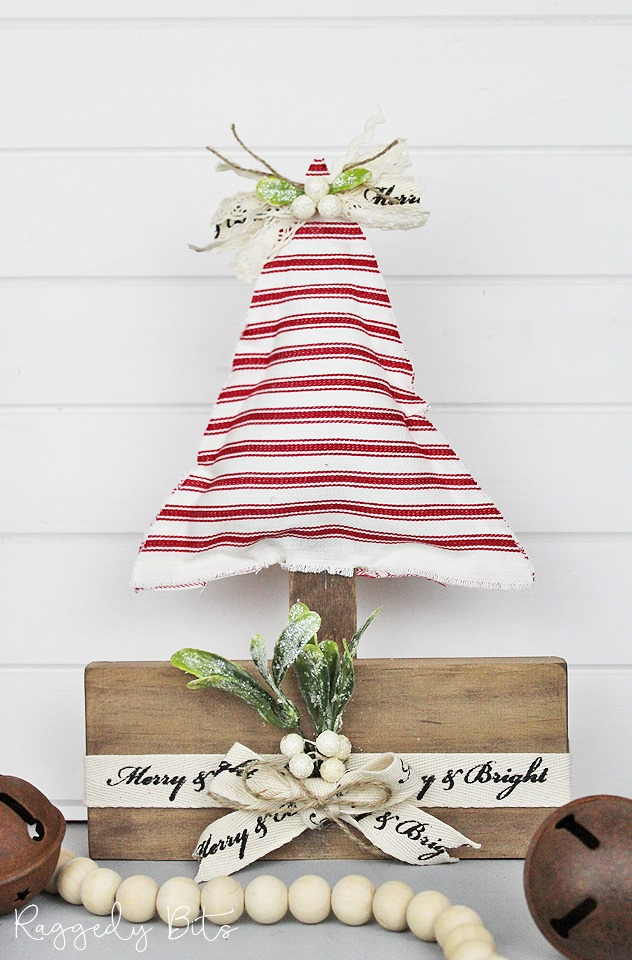 A red and white ticking fabric Christmas tree with wooden stand.