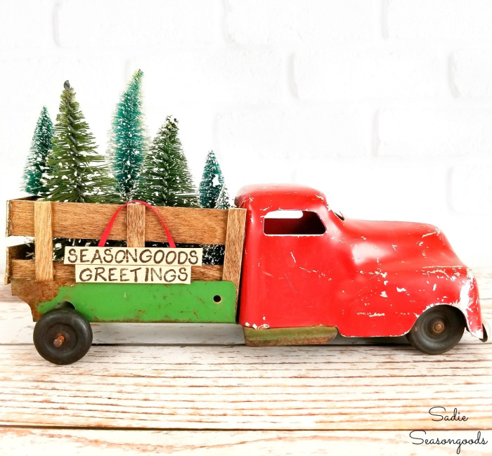 An old cheap truck upcycled for Christmas. The truck is red, very old with wood box and lots of trees