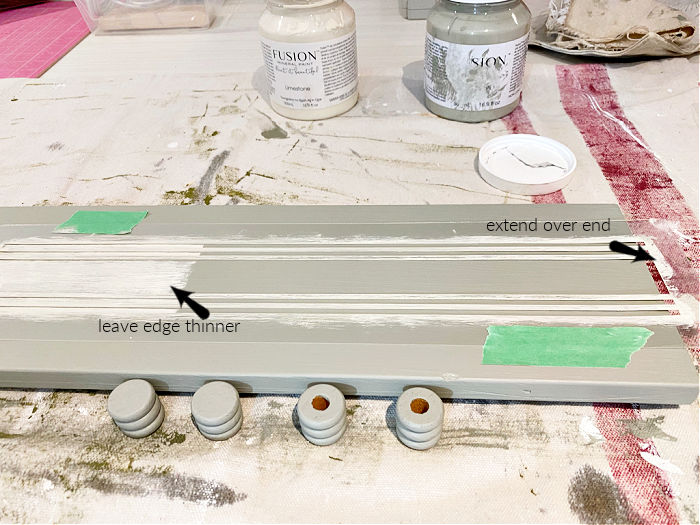 Placement of a grain sack stencil on a eucalyptus green painted table riser project, with arrows giving placement tips